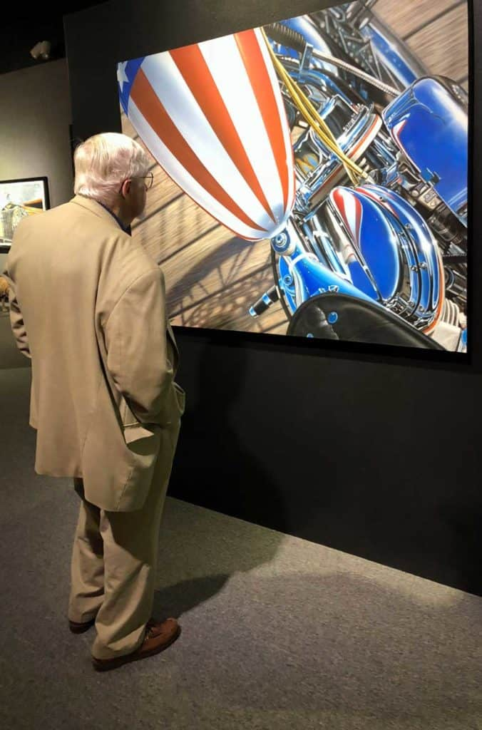 An art patron looks over AMERICA painting at MOAS 2018